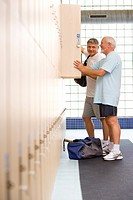 Two men using lockers in gym, side view (thumbnail)