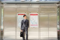 Businessman with briefcase by maps on wall outdoors