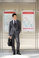 Businessman with briefcase and newspaper listening to MP3 player, by maps on wall