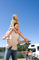 Girl 9-11 on father's shoulders, mother and brother 10-12 by motor home in background, low angle view