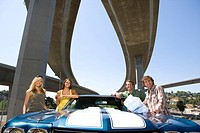 Two young couples by car beneath overpass, smiling, portrait, low angle view