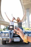 Young woman taking photograph of friends on bonnet of car beneath overpass, close-up of hand