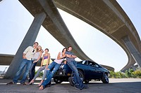 Medium group of friends on bonnet of car beneath overpass, smiling, portrait, low angle view