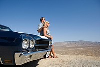 Young couple by car in desert looking at view, low angle view