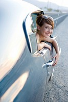 Young woman leaning out of window of car, smiling