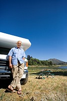 Mature man by motor home and portable picnic table, smiling, portrait, low angle view (thumbnail)