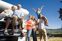 Family of three generations by motor home and lake, smiling, portrait, low angle view
