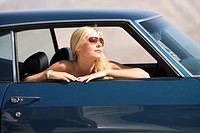 Young woman in sunglasses in car, looking out window, side view