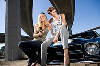 Two young women on bonnet of car beneath overpass, smiling, low angle view
