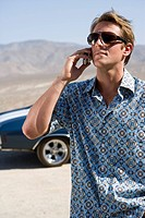 Young man in sunglasses using mobile phone by car in desert