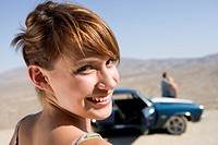 Young woman in desert by car and friends, smiling, portrait, close-up