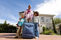 Father with son and daughter8-10 holding suitcase outdoors by house, smiling, portrait, low angle view