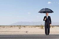 Businessman with umbrella on open road in desert, portrait, low angle view (thumbnail)