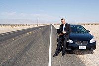 Businessman by car on open road in desert, using laptop computer, portrait