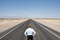 Businessman in middle of road in desert, hands on hips, rear view