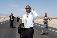 Small group of businessmen and women using mobile phones on road in desert, low angle view