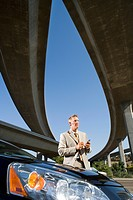Businessman using electronic organiser by car beneath overpasses, low angle view