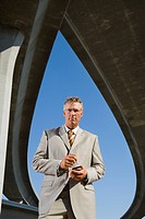 Businessman with electronic organiser beneath overpasses, portrait, low angle view