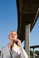 Businesswoman using mobile phone beneath overpass, low angle view