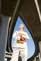 Businesswoman holding folder beneath overpasses, low angle view