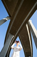 Businesswoman using binoculars beneath overpasses, low angle view