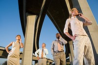 Small group of businesspeople using mobile phones beneath overpasses, low angle view