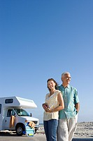 Mature couple arm in arm by motor home on beach, smiling, low angle view