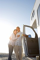 Mature couple arm in arm by motor home on beach, smiling, low angle view sun flare (thumbnail)