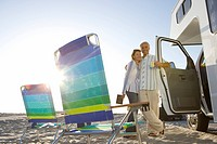 Mature couple arm in arm by motor home on beach, portable chairs in foreground, low angle view sun flare