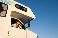 Mature woman looking out window of motor home, smiling, portrait, low angle view (thumbnail)