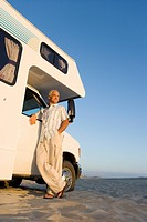 Mature man by motor home on beach, arm on door, low angle view