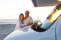 Mature couple embracing by motor home on beach, smiling, portrait, dusk