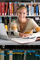 Woman studying with laptop computer in library, smiling, portrait