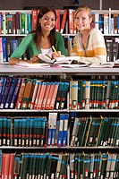 Two young women studying in library, smiling, portrait
