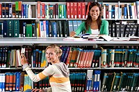 Young woman studying in library by friend taking book from shelf, smiling, portrait