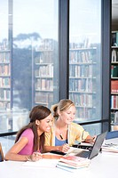 Female students studying with laptop computer in library, smiling, side view