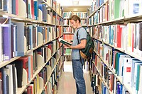 Young man with rucksack looking at book in library, side view