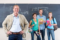 Teacher and students by blackboard in classroom, smiling, portrait