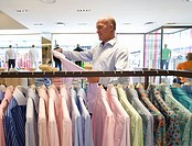 Mature man looking at shirt in shop, side view (thumbnail)