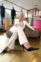 Mature woman in shop, legs crossed, portrait (thumbnail)