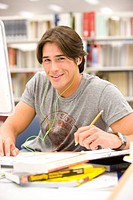 Young man with earphones sutdying in library, smiling, portrait