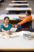 Young man and woman studying in library, man smiling at woman, elevated view