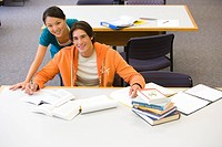 Young woman standing behind young man studying in library, smiling, portrait, elevated view