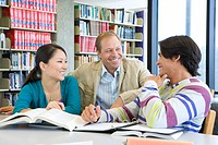 Mature man smiling at young man studying with friend in library