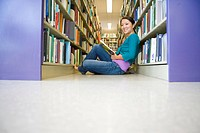 Young woman sitting on floor in library, low angle view
