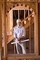 Architect with blueprint in partially built house, smiling, portrait