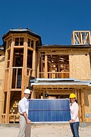 Man and woman in hardhats with solar panel by partially built house, portrait