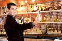 Young man by bar with drink, taking photograph, smiling