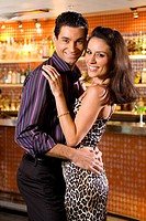 Young couple embracing in bar, smiling, portrait