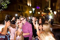 Young couple arm in arm surrounded in paparazzi, smiling (thumbnail)